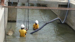 Workers at the intake pond of the FloWater Resources (Iloilo) Inc. use a vacuum hose to suck sludge from the bottom to keep its depth at optimum level and ensure uninterrupted flow of raw water into its pumping stations.